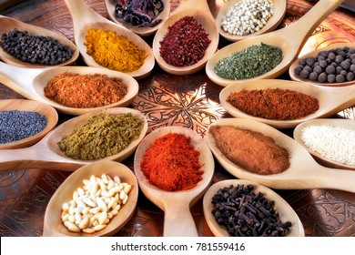 Spices and herbs of different colors in wooden spoons on lacquered oriental carved table, viewed from high angle in close-up.