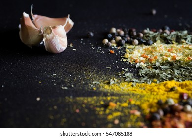 Spices, herbs and garlic on a black background