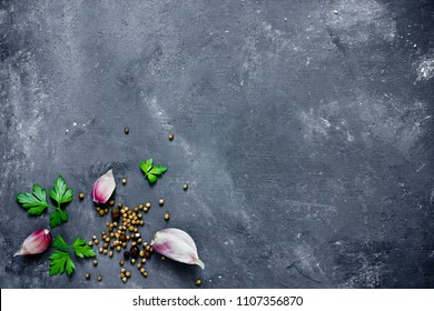 Spices, herbs and greens ingredients for cooking food background on black slate table top view