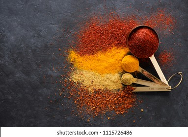 Spices and herbs in measuring spoons on a black background, top view