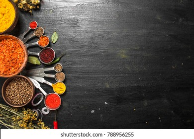 Spices and herbs with measuring spoons. On the black chalkboard.