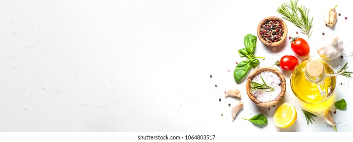 Spices, herbs and olive oil over white stone table.