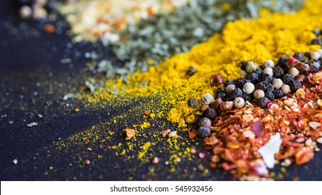 Spices and herbs on a black background - Shutterstock ID 545932456