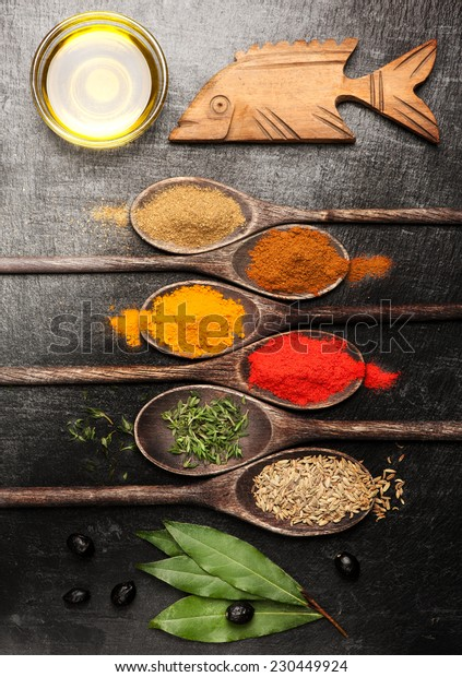 Spices and herbs on black stone background. Spices for seafood.