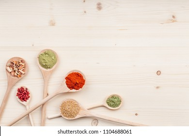 spices and herbs on kitchen wooden table background with copy space for text. food, cooking and restaurant concept. flat lay colorful composition, top view