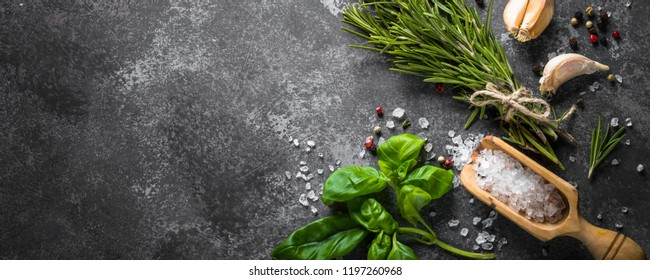 Spices and herbs over black stone table. Food background. Long format.