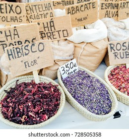 Spices, herbs, petals of flowers, tea leaves on a bio market, with names in portuguese. Hibisco flor - flower of hibiscus, cha preto - black tea, abacate folha - leaves of avocado