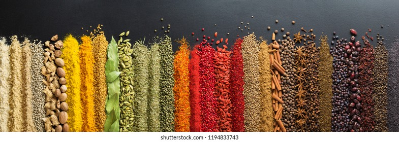 Spices and herbs for website headers. Seasoning scattered on black table, background for packing with food.