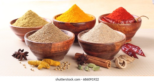 Spices and herbs in wooden bowls. Food and cuisine ingredients. Colorful natural additives.