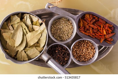 Spices in metal containers. Bay leaves, cumin, pepper and cloves.