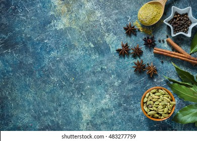 Spices on blue stone background with space for text. Selective focus.