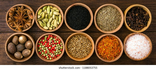 Spices on a wooden background in bowls, place of copying, seasoning, saffron, cumin, black sesame, cardamom, nutmeg, pink salt, star anise, coriander, long banner