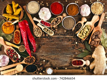 Spices on wooden background. Copy space. Top view. Different pepper powder and peppercorns, ginger, red hot chili pepper, turmeric, saffron, cardamon, sea salt, coriander, bay leaf, cloves, kalonji.