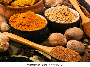 Spices on wooden background. Ginger, turmeric powder in cups and roots, kalonji, bay leaf, nutmeg.