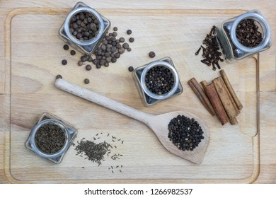 spices on a wooden board such as caraway, pepper and cinnamon with a spoon  - Shutterstock ID 1266982537