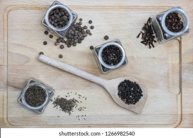 spices on a wooden board such as caraway, pepper and cinnamon with a spoon  - Shutterstock ID 1266982540