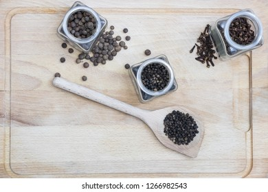 spices on a wooden board such as caraway, pepper and cinnamon with a spoon  - Shutterstock ID 1266982543