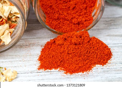 Spices pouring out of the jar. Dried ground paprika.