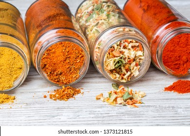 Spices pouring out of jars lying on a wooden counter. freeze-dried vegetables, ground paprika, curry and spice mixes.