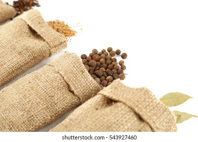 Spices in sacking bags on white background, closeup
