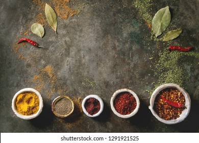 Spices seasoning and herbs variety in ceramic bowls in row. Different ground peppers, chili pepper, turmeric, bay leaf, cinnamon over dark metal background. Flat lay, space. Cooking concept