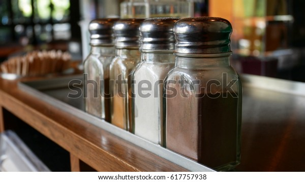 Spices and seasonings for coffee in cafe. Spice bottle For sprinkle a drink. Contains cocoa, cinnamon, white sugar And brown sugar.