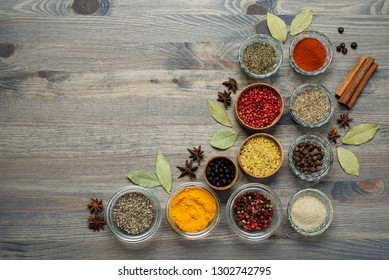 Spices and seasonings on the gray wooden background. Place for text.