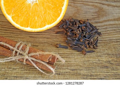 Spices and sliced fresh orange on a wooden table. Ripe orange, Cinnamon sticks and cloves on wooden background, close up.