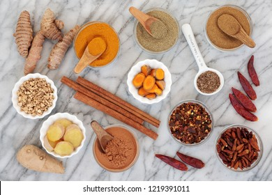 Spices for slimming with turmeric, cumin, ginger, chilli, cinnamon and gymnema sylvestre used to suppress appetite. Top view on marble background.