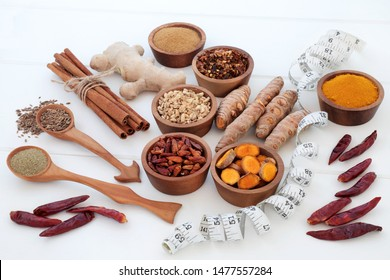 Spices for slimming and weight loss with fresh and dried turmeric, cumin, ginger, chilli, cinnamon and gymnema sylvestre used to suppress appetite. Top view on white wood background.