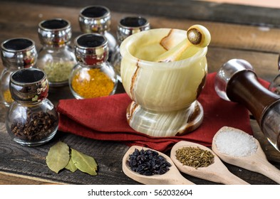 spices in spoons and Jar with mortar on wodeen background
