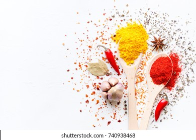 Spices in spoons and scattered on a white background with space for text