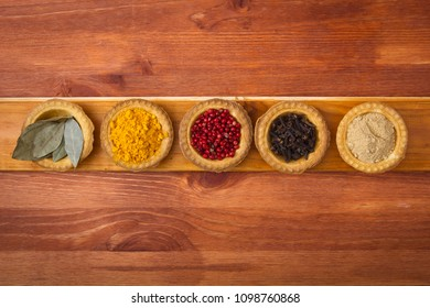 Spices in tartlets on a wooden background