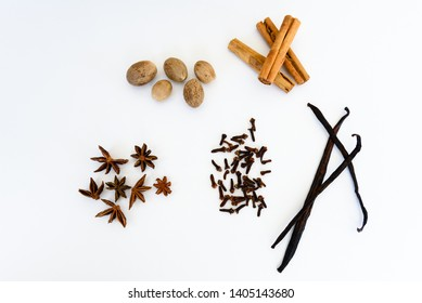 Spices used in cooking, often for Christmas baking, whole nutmeg, cinnamon quills, cloves, star anise and vanilla beans. Flat lay isolated on white