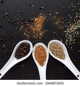 Spices were scattered on the black wooden table. Measuring spoon. Cooking and seasoning for taste