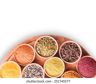 spices in a wooden bowl on white background