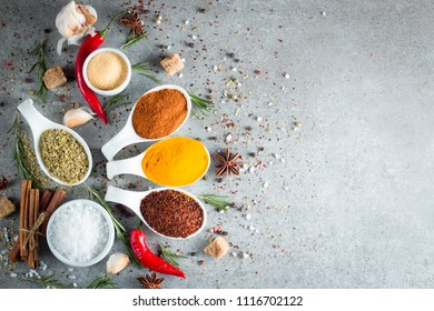 Spices in Wooden spoon. Herbs. Curry, Saffron, turmeric, rosemary, cinnamon, garlic, pepper, anise on wooden rustic background. Collection of spices and herbs. Salt, paprika. Copy space. Top view. Ban