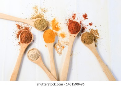 spices in wooden spoon on white background