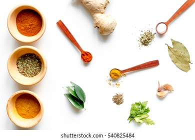 spices in wooden spoons on white background top view