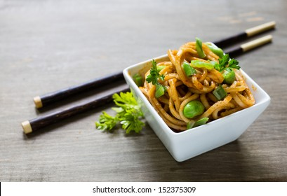 Spicy asian noodle dish with chopsticks.