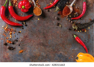 Spicy background with assortment of different hot chili and allspice peppers over old rusty iron background. Top view. With copy space