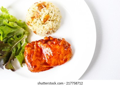 Spicy barbecue chicken steak served with fried garlic rice and vegetables