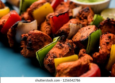 Spicy barbecued Chicken Tikka Boti on skewers served in a plate with green chutney - selective focus