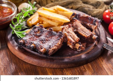 Spicy barbecued pork ribs served with french fries on chopping board