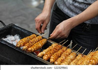Spicy barbecued tofu kebabs being prepared by street food vendor in Chinese market