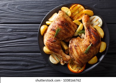 Spicy bbq chicken legs with grilled oranges, onions, garlic and potatoes close-up on a plate on a table. horizontal top view from above