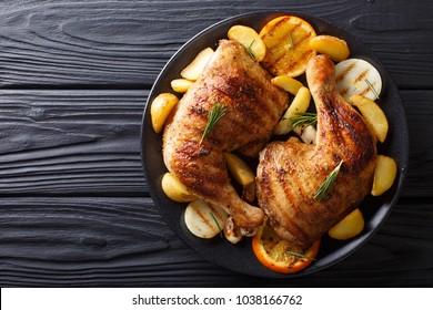 Pittige bbq kippenpoten met gegrilde sinaasappels, uien, knoflook en aardappelen close-up op een bord op een tafel. horizontaal bovenaanzicht van bovenaf
