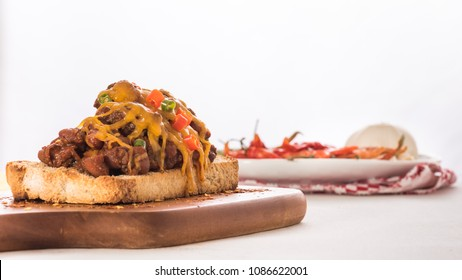 Spicy beef and bean chili on toast covered in melted cheddar cheese