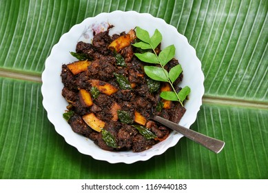 Spicy beef fry South Indian dish Kerala, India. side dish of ghee rice, appam, parotta, puttu, bread and chappathi, Kerala cuisine ,Buffalo roast, Meat pepper fry with coconut. India spices cooking