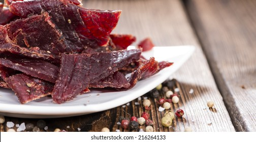 Spicy Beef Jerky on vintage wooden background (close-up shot)